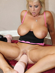 Big tittied blonde sitting on some big fat dildos