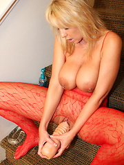 Slut in red body stocking fucks her ass with a glass dildo